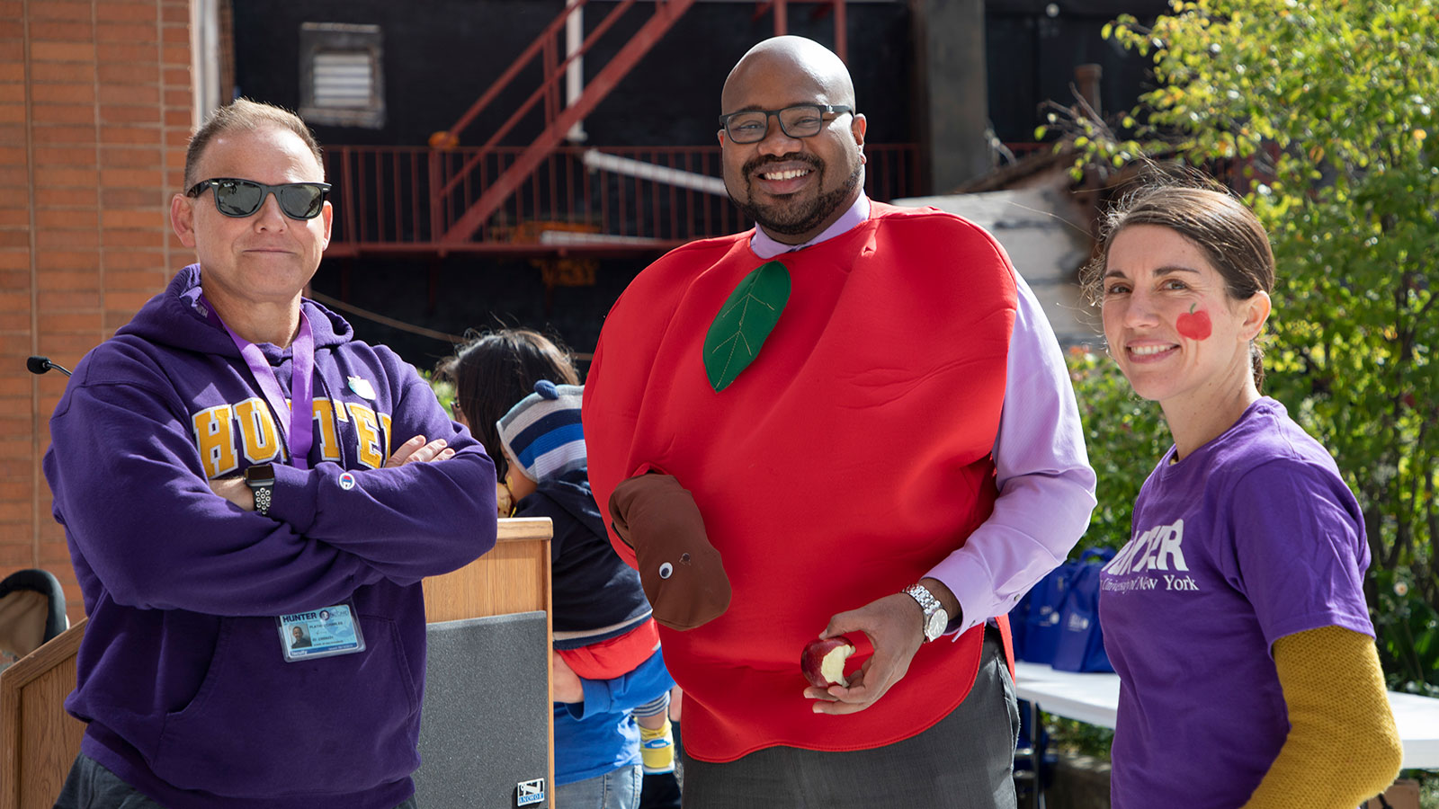 3 people holding apples for big apple crunch