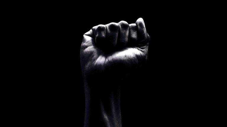 raised fist on black background.