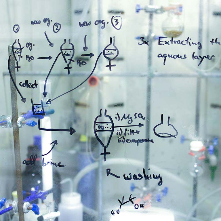 lab notes written on glass panel in lab setting