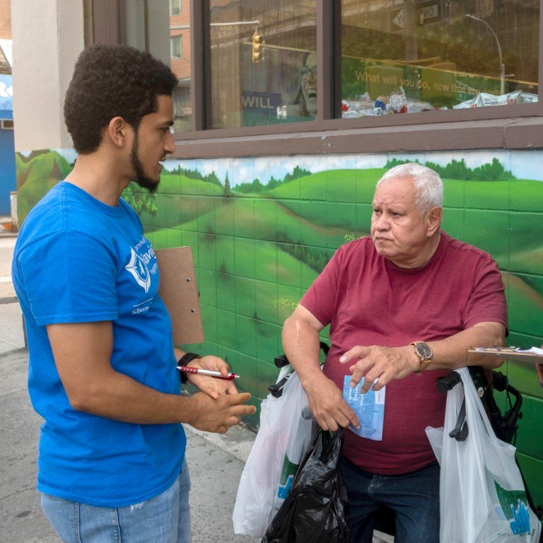 man with clipboard talking to man in wheelchair