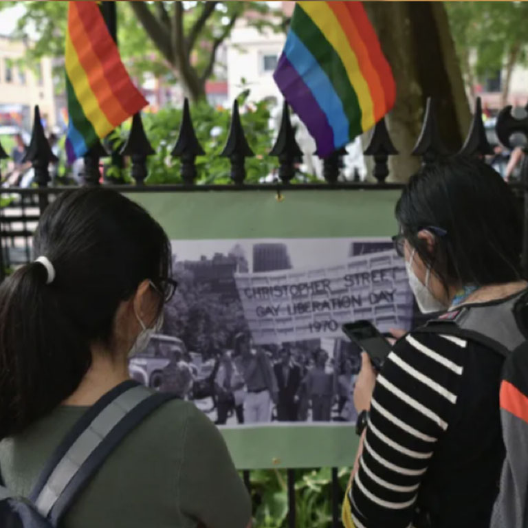 Two people standing in front of LGBTQ flags
