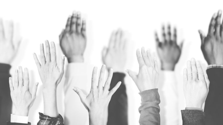 black and white image of raised hands.