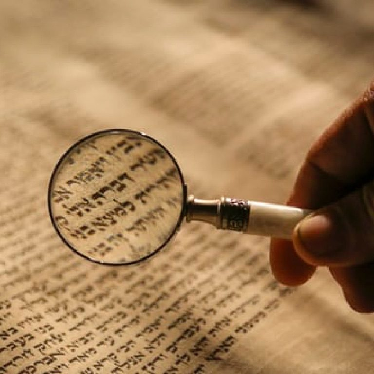 open hebrew book and magnifying glass