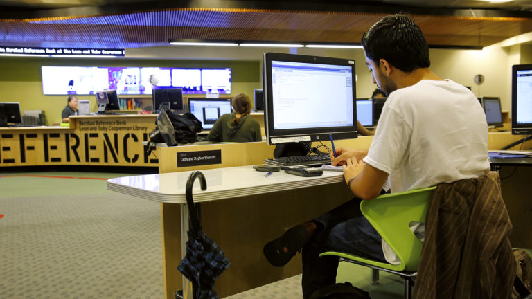 student at computer in new library