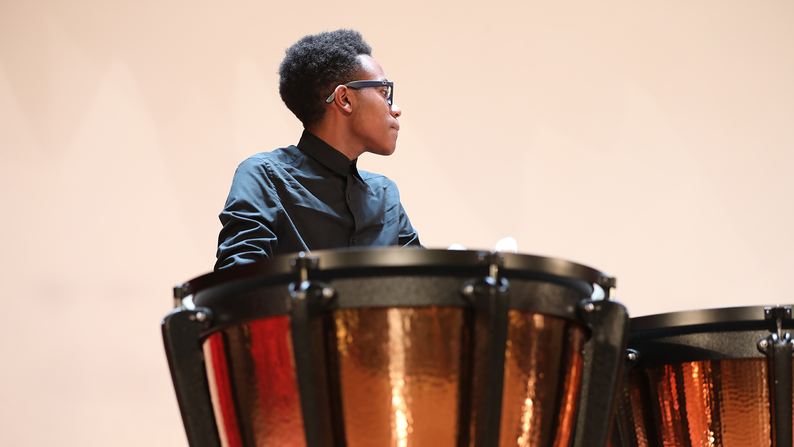 student next to a drum