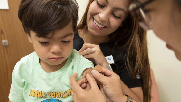 Nurse putting band aid on boy
