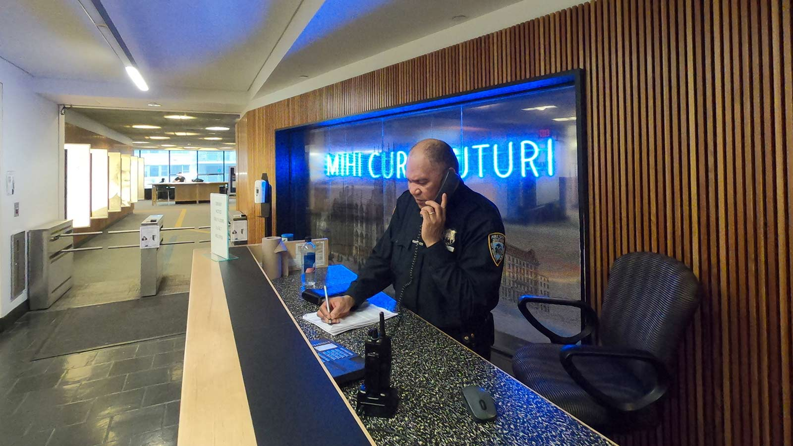 Security person at front desk on phone
