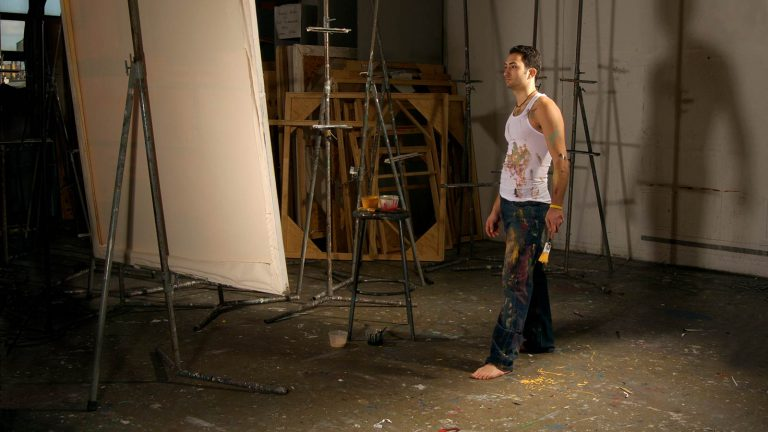 art student in art studio in front of a large canvas