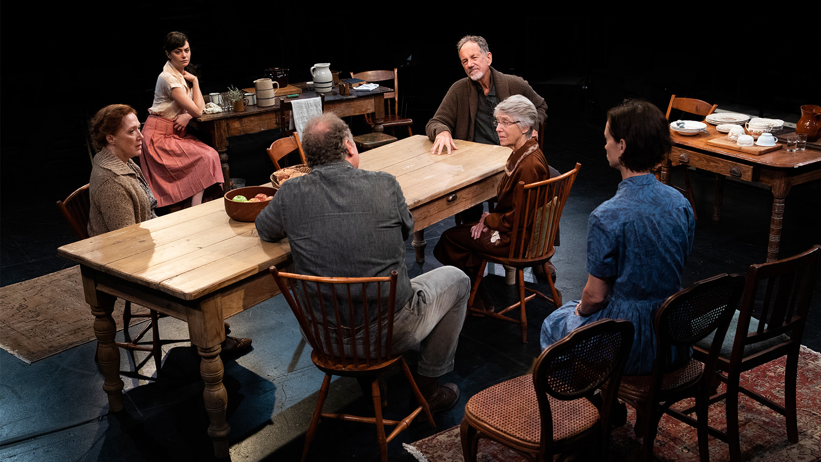 Performers from the production of Uncle Vanya having a discussion around the table